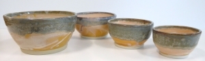 Four bowls with shino and red iron glazes.
