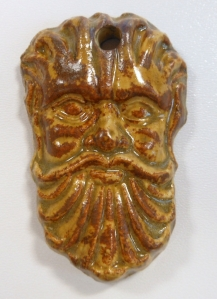 Ceramic medallion of bearded man brush glazed with red iron and fired to cone 6.