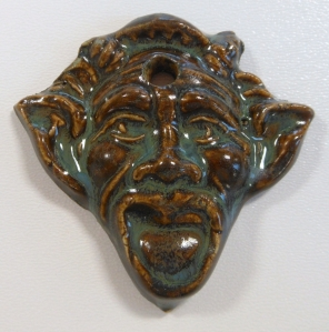 Press molded gargoyle face glazed with floating green over plainsman m370 clay.