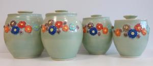 Four celadon and slip decorated ceramic jars.
