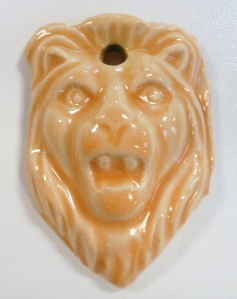 Small press molded ceramic lions face medallion.