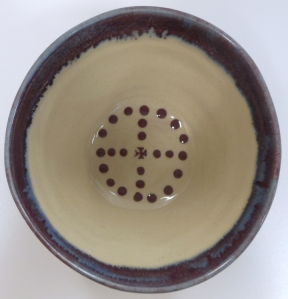 Slip decorated bowl with small medieval cross and purple glaze.