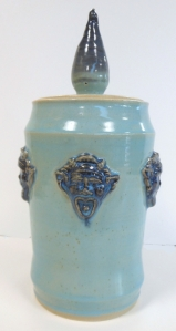 Recycled clay jar with lid decorated with medieval gargoyles.