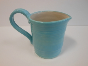 A small wheel thrown jug with brushed aqua slip, robins egg blue and white glazes.