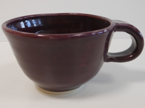 Pottery wheel thrown cappuccino cup decorated with a deep eggplant purple glaze.