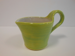 A small wheel thrown pitcher with pulled handle decorated with coloured slip.