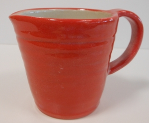 Small wheel thrown red slip coated pitcher with clear glaze.