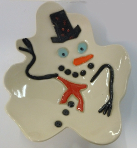 Hand built melted snowman serving plate. Formed and cut black clay on M370 white stoneware with slip and clear glaze.