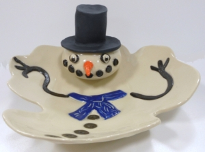 Snowman with wheel thrown head attached to a drape molded plate surface.