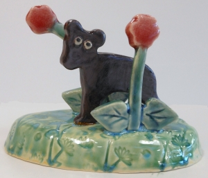 Folk art ceramic sculpture of bear cub.