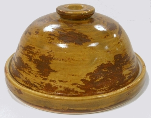Wheel thrown covered dish with a modified berry rust glaze and antique white glaze interior finish.