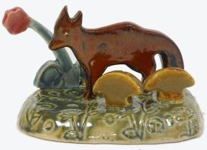 Folk art red fox sculpted in ceramic.