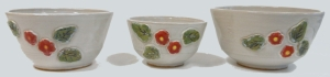 Nesting bowls decorated with hand cut relief petals and flowers, slip and glaze coloured.
