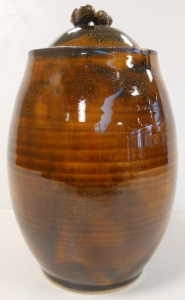 Wheel thrown pottery jar with two small slip cast acorns.