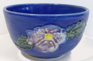 Wheel thrown bowl with cobalt blue glaze and pansy pattern in the style of Moorcroft pottery.