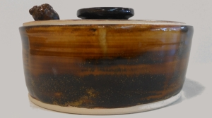 Wheel thrown covered casserole baking dish glazed with amber brown.