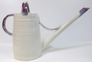 Handmade pottery garden watering jug, decorated with antique white and purple glazes.