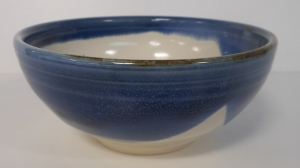 Matcha tea bowl decorated with floating blue over antique white glaze.