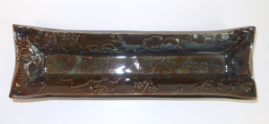 Handmade olive tray with embossed floral pattern and decorated with floating blue glaze.