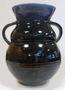 Wheel thrown pottery vase with hand pulled handles decorated with floating blue glaze.