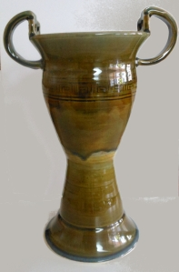 Pottery wheel thrown urn decorated with forest green and amber glazes.
