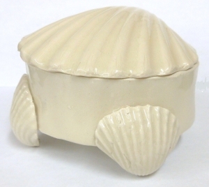 A small hand made ceramic box decorated with pottery shells.