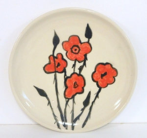 Remembrance Day commemorative plate.   Wheel thrown and decorated with coloured slip depicting poppies.
