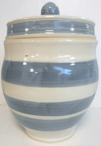 Pottery jar inspired by Cornish Ware with slip stripes and glazed in antique white .