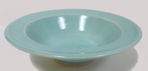 A small wheel thrown pottery bowl decorated with robins egg blue glaze