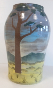 A large vase with hand painted coloured clay slip depicting trees on the savanna.