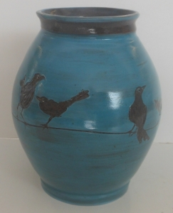 A large blue slip decorated vase depicting  crows on a wire.